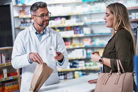Image of a pharmacist helping a retail customer